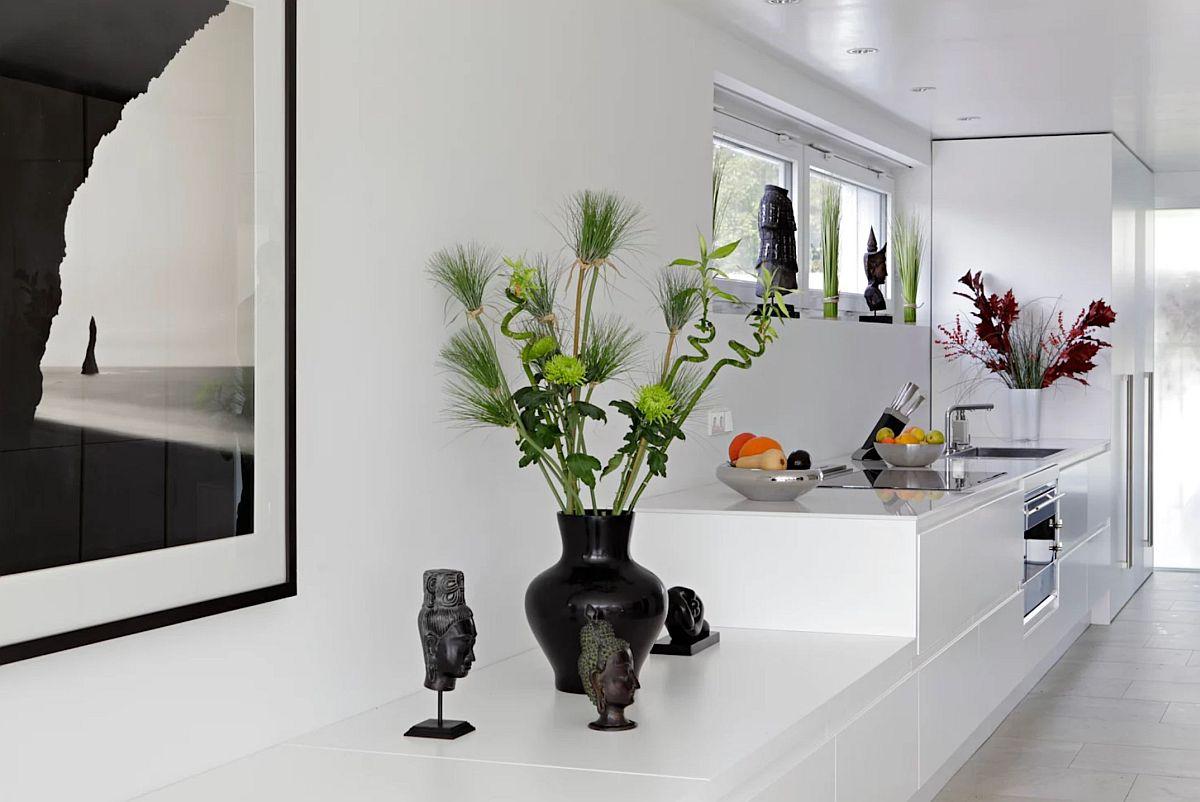 Mobilierul de pe o latură a casei, unde sunt funcțiunile de hol, bucătărie și comodă sufragerie este unitar, un ansamblu alb configurat în trepte.