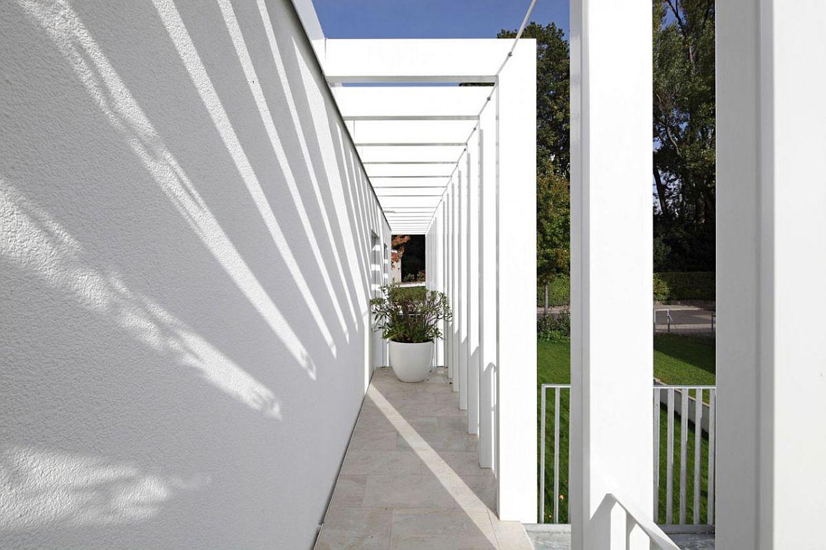 Vedere de pe scara fațadei laterale către terasă și stradă. Se poate observa jocul de lumini și umbre dat de structura metalică ce îmbracă construcția și care dinamizează arhitectura.