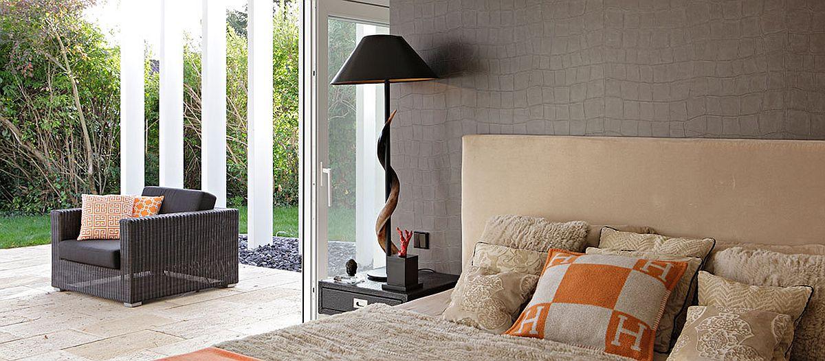 Dormitorul matrimonial beneficiază de deschidere către terasa demisolului aflată la același nivelul cu grădina din spatele casei.