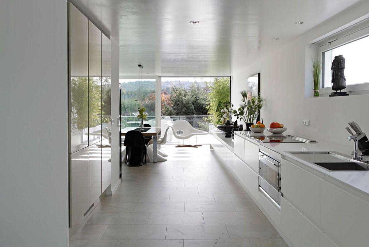 Frontul de lucru din bucătărie se continuă către zona de terasă, lumina naturală fiind asigurată practic din toate părțile.