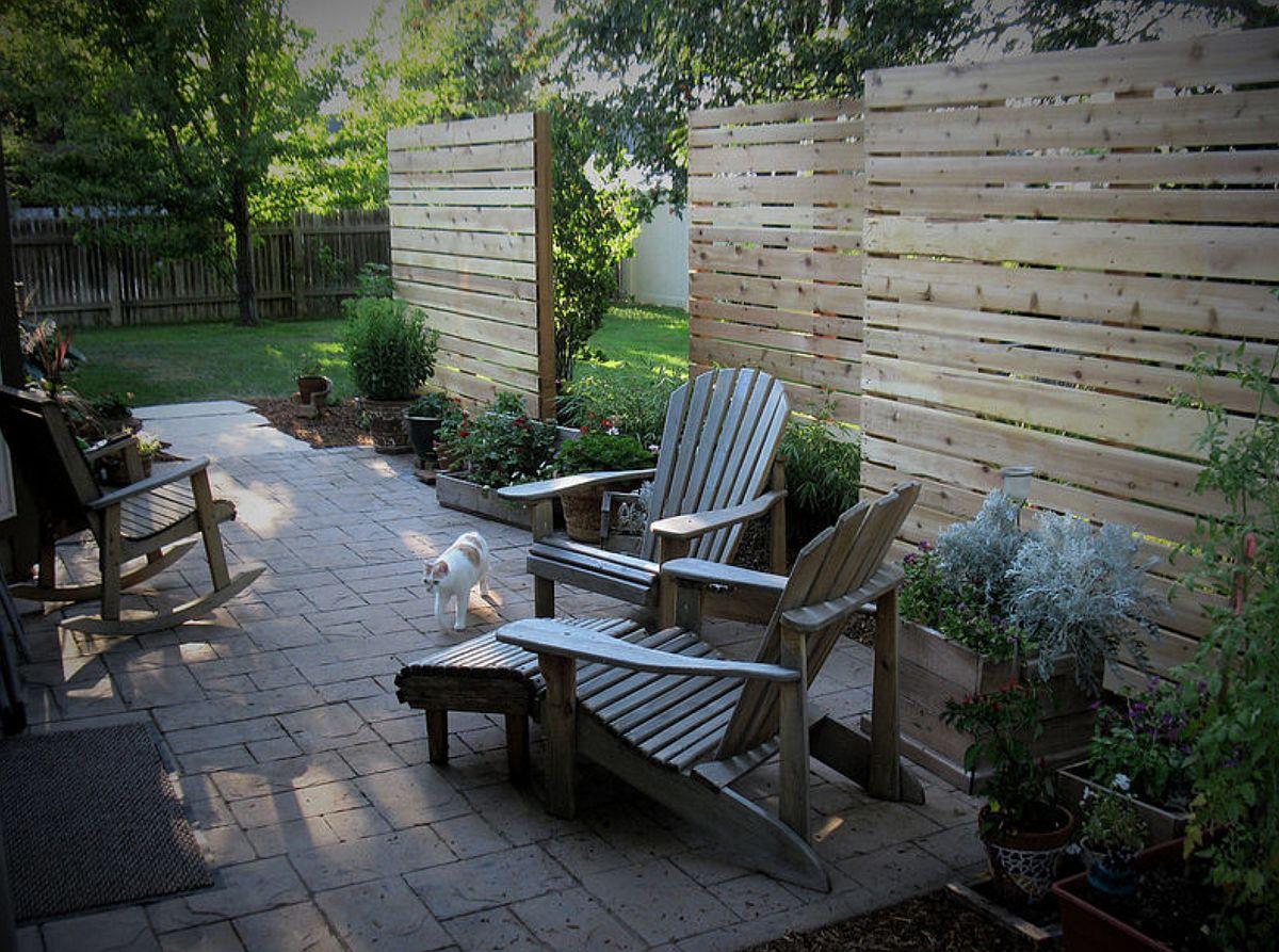 Nu vrei să se vadă nimic nimic către locul de terasă dinspre vecini? Foarte bine, paravane intercalate, dar realizate din două rânduri de material, ca niște ziduri din lemn pot fi o soluție bună. De ele pot fi agățate jardiniere cu flori sau decorațiuni de exterior. Foto Farwest Landscape Design