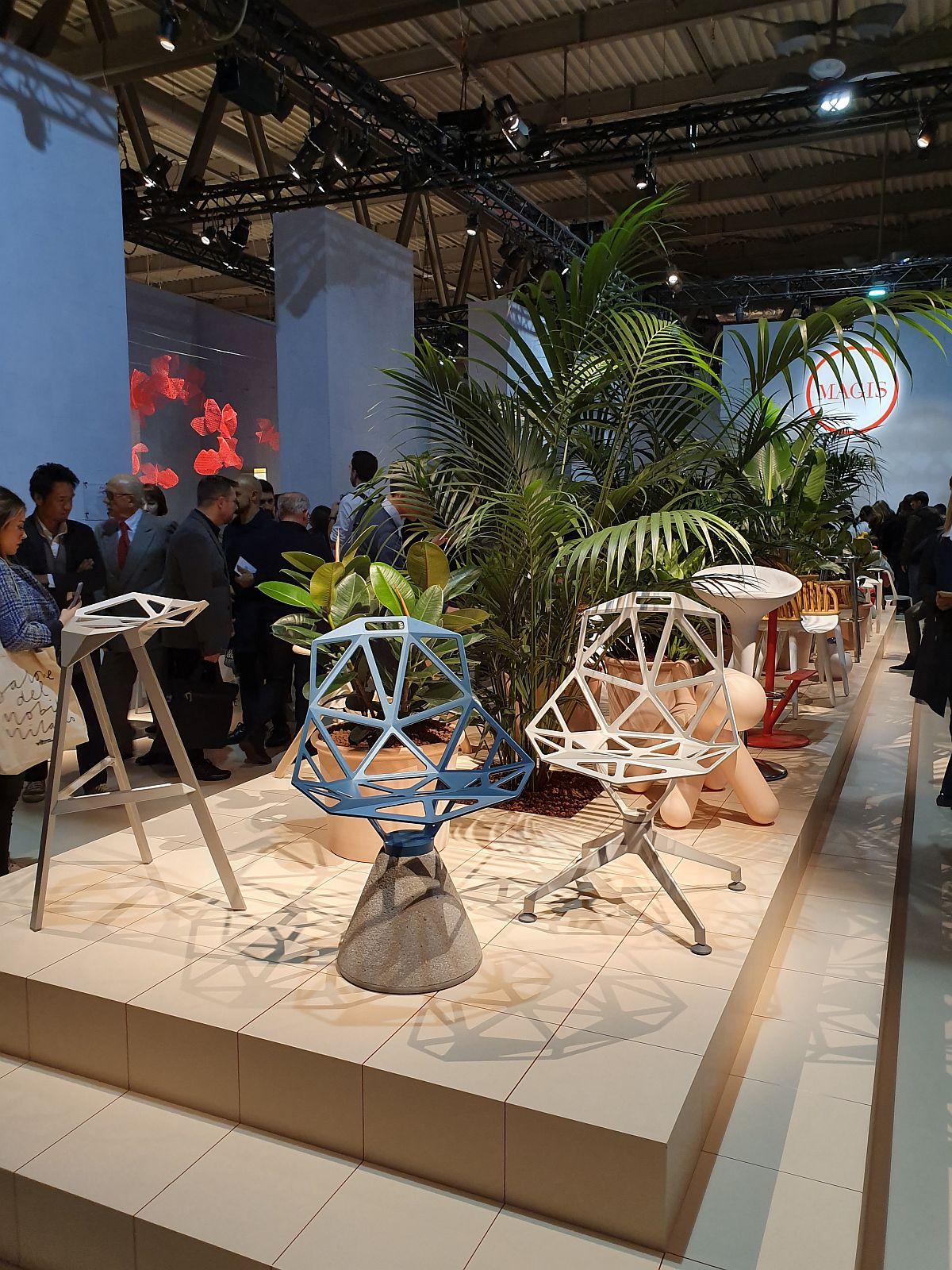 Podium pentru scaune emeblematice, dar toate împănate cu plante în standul Magis.
