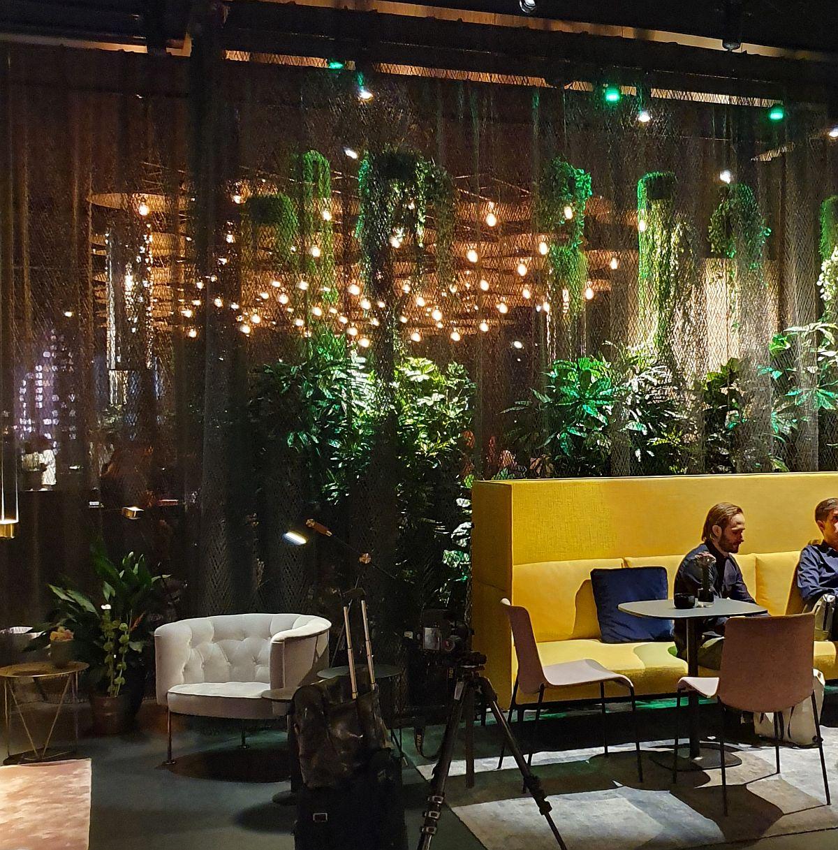 Zona de cafeterie din standul Walter Knoll delimitată cu plase metalice și plante. Plus lumini plăcute pentru atmosferă plăcută.
