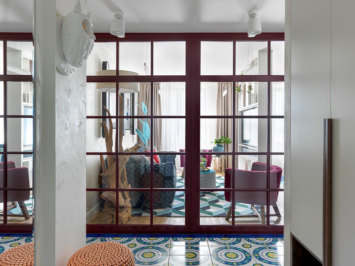 De la intraea în locuință se vede spațiul livingului, care este însă parțial separat de tâmplărie roșie cu geamuri transparente. La nivelul pardoselii în holul locuinței s-au folosit plăci ceramice colorate, astfel că din start există un contrast de roșu-albastru-alb care impresionează.