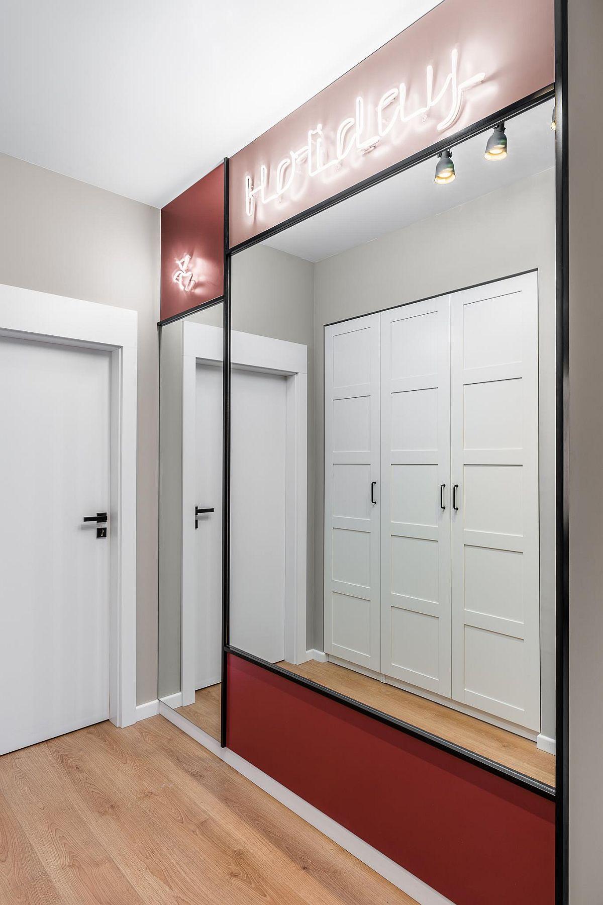 La intrarea în locuință ceea ce se vede este panoul cu oglinzi, ceea ce dă senzația de spațiu mai luminos și mai mare. În hol există un spațiu de depozitare închis, configurat încastrat în perete.