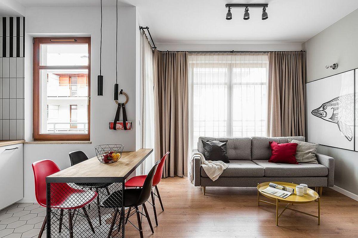 Cel mai spațios spațiu din casă este cel al zonei de zi, care beneficiază și lumină naturală din plin. Pentru a păstra un aspect cât mai aerisit, arhitecții au propus un număr strict necesar de piese de mobilier pe un fundal neutru al finisajelor, respectiv parchet, plăci ceramice albe pentru pardoseala bucătăriei și alb cu zone de gri deschis pentru zugrăveala pereților. Decorațiunile textile sunt și ele minimale, dacă la bucătărie a fost ales stor pentru zona de zi fereastra este îmbrăcată cu perdele albe și draperii într-o nuanță neutră, cât mai aproape de cea a parchetului, dar covoarele lipsesc tocmai pentru a da senzația de mai mult spațiu și pentru a limita fragmentările.