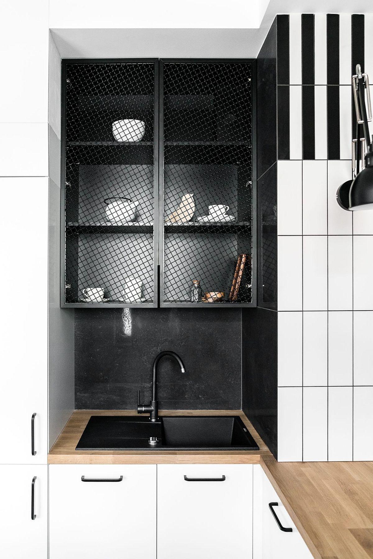 Pentru a atenua caracterul tehnic al bucătăriei, zona de chiuvetă a fost tratată ca o nișă. Negrul îi onferă un efect de adâncime, dar și maschează dulapul cu plasă din sârmă prevăzut aici.