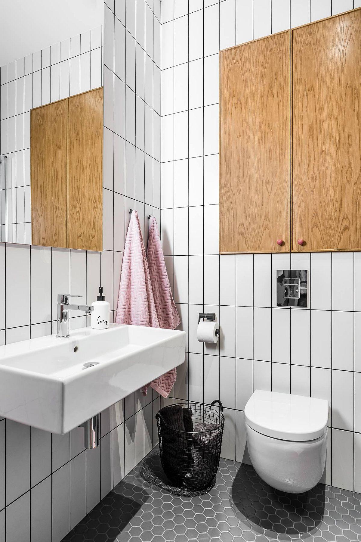 Deasupra rezervorului vasului de toaletă, care este îngropat, a fost creată o nișă de depozitare, mascată cu uși similare celor din lemn, suprafețe care sparg grafica imprimată de desenul plăcilor ceramice.