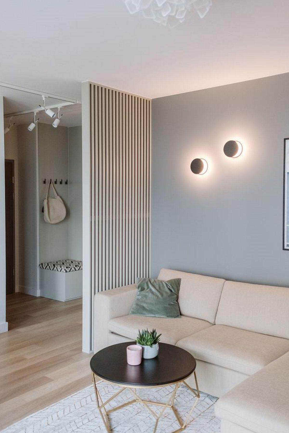 Intrarea în locuință se face pe un hol mic din care se vede direct livingul. Proprietarii și-au dorit mai multă intimitate, așa că arhitecții au prevăzut o delimitare parțială cu un ansamblu de riflaje, realizate pe comandă, în dreptul canapelei.