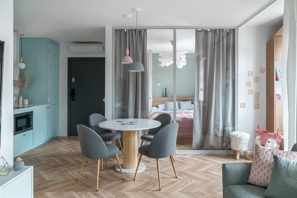 În afara dormitorului și camerei de baie, restul funcțiunilor comunică liber. Ușa de acces în locuință este singurul element închis la culoare, restul amenajării finnd pe tonuri neutre, cu accente de turoaz în zona bucătăriei și tușe de roz pentru accesorii textile. Locul de masă este la granița dintre zona de noapte și cea de zi, ca atare s-a ales un mobilier mai prietenos, masă rotundă și scaune tapițate.