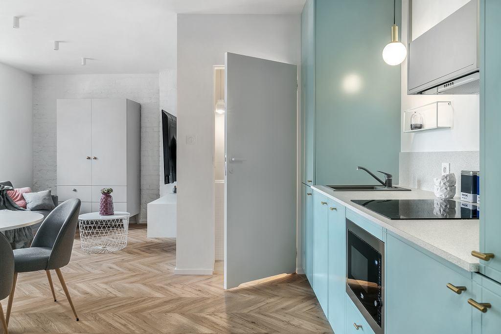 Camera de baie este învecinată cu bucătăria, dar evident separată cu ușă. O parte din pereții locuinței au fost lăsați cu cărămida vechilor ziduri renovate la vedere și ulterior vopsită în alb, pentru un plus de textură. Și ușa interioară a băii a fost aleasă albă pentru a nu face contrast cu finisajul pereților.