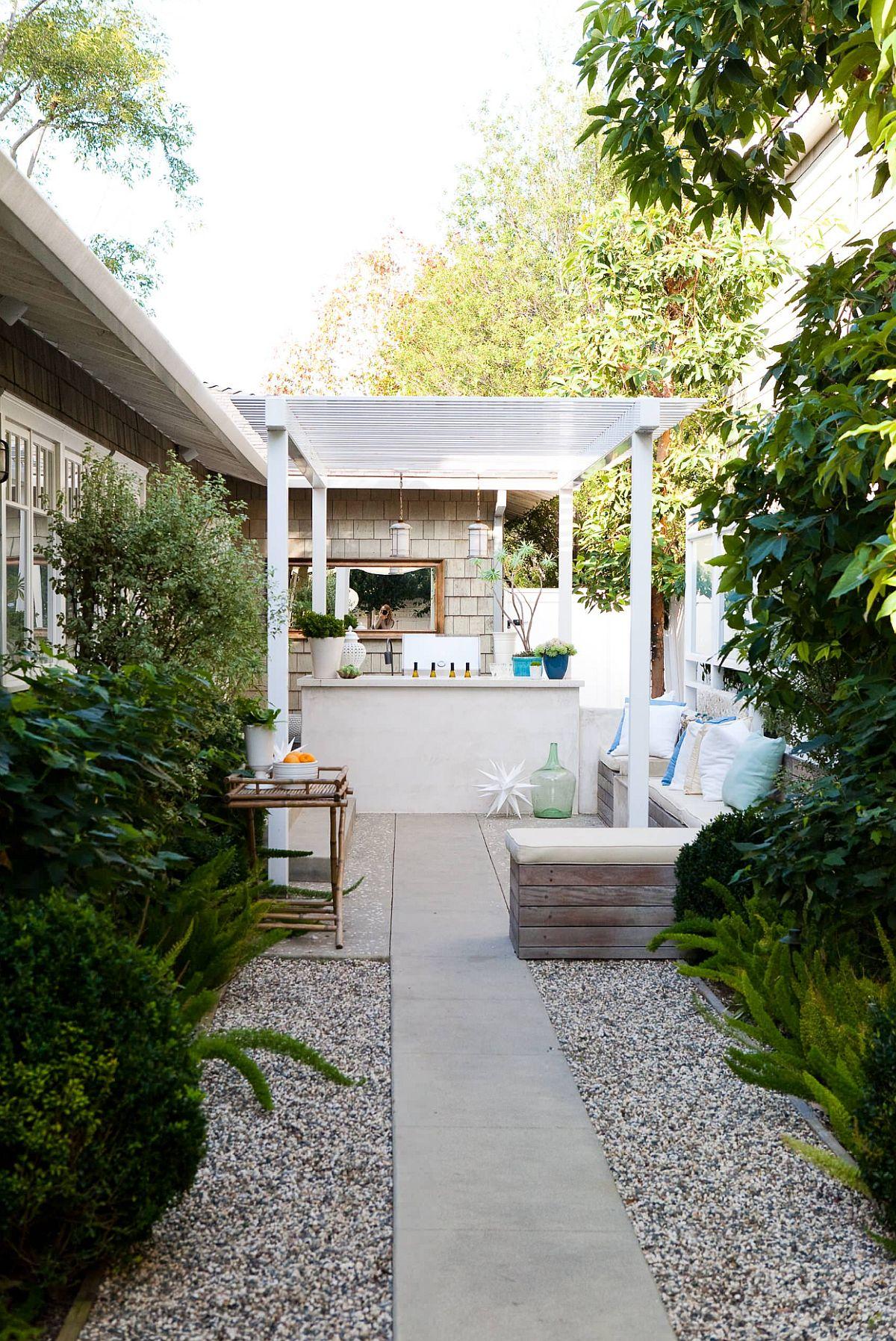 Alee din dreptul accesului în casă se continuă pe lângă construcție și este încadratp cu pietriș, iar mai departe, pe verticală este plantată vegetație.