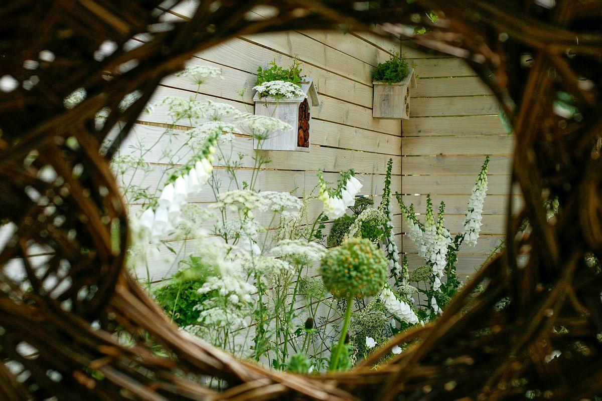 De la interiorul cuibuluil împletit destinat lecturii și relaxării se vede mare parte din gard, care este și el decorat.