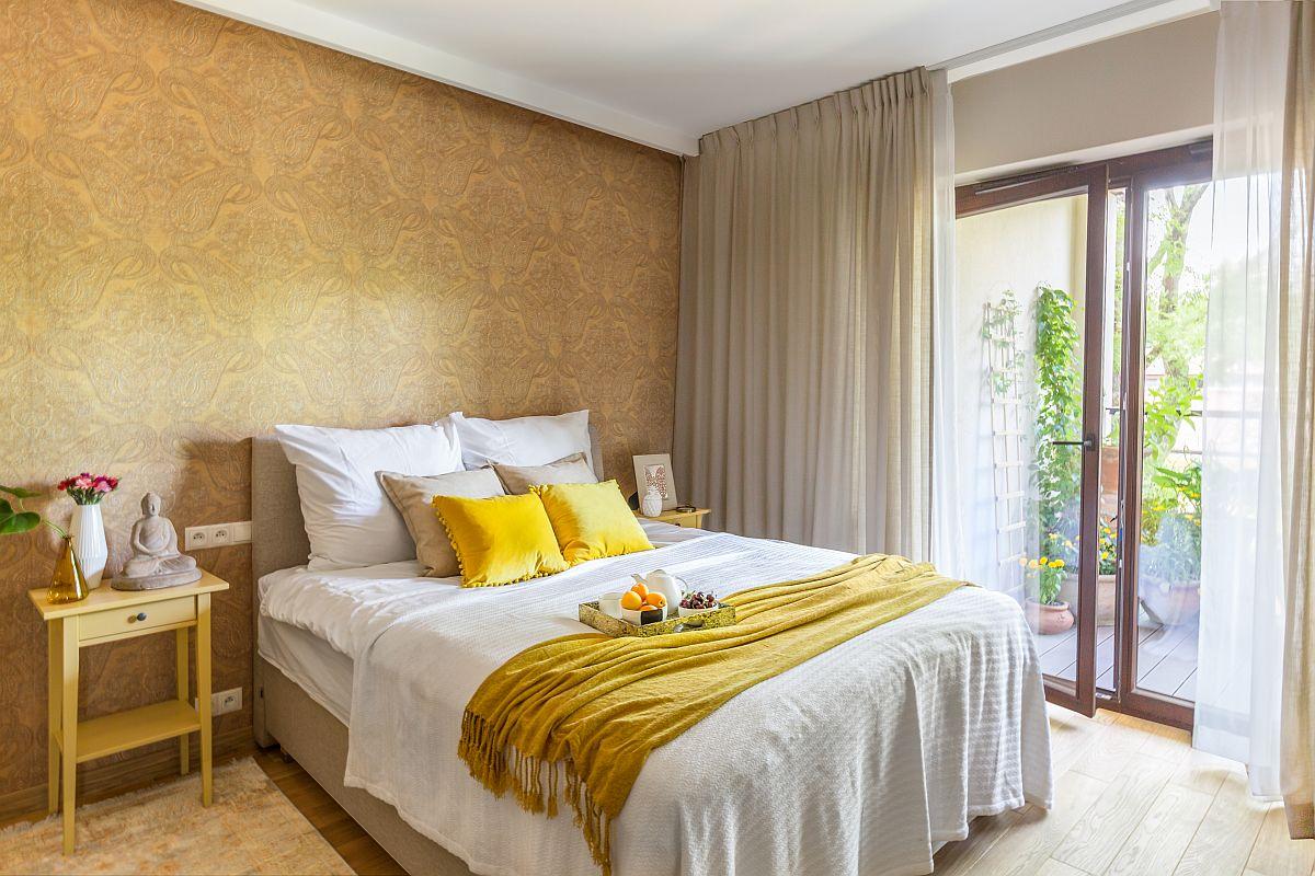 Dormitorul matrimonial, la fel ca și zona de zi, beneficiază de acces către terasă. Ambientul cald și calm este simplu, dar cu efect conturat de finisaje aproapiate ca tonuri de culoare. Un tapet cu motive indiene este ales în nuanță similară parchetului, iar lejeria de pat și perdelele albe dau nota de cuățenie și serenitate. În acest cadru accentele de galben înviorează atmbianța alături de verdele plantelor care se văd pe ferestre.