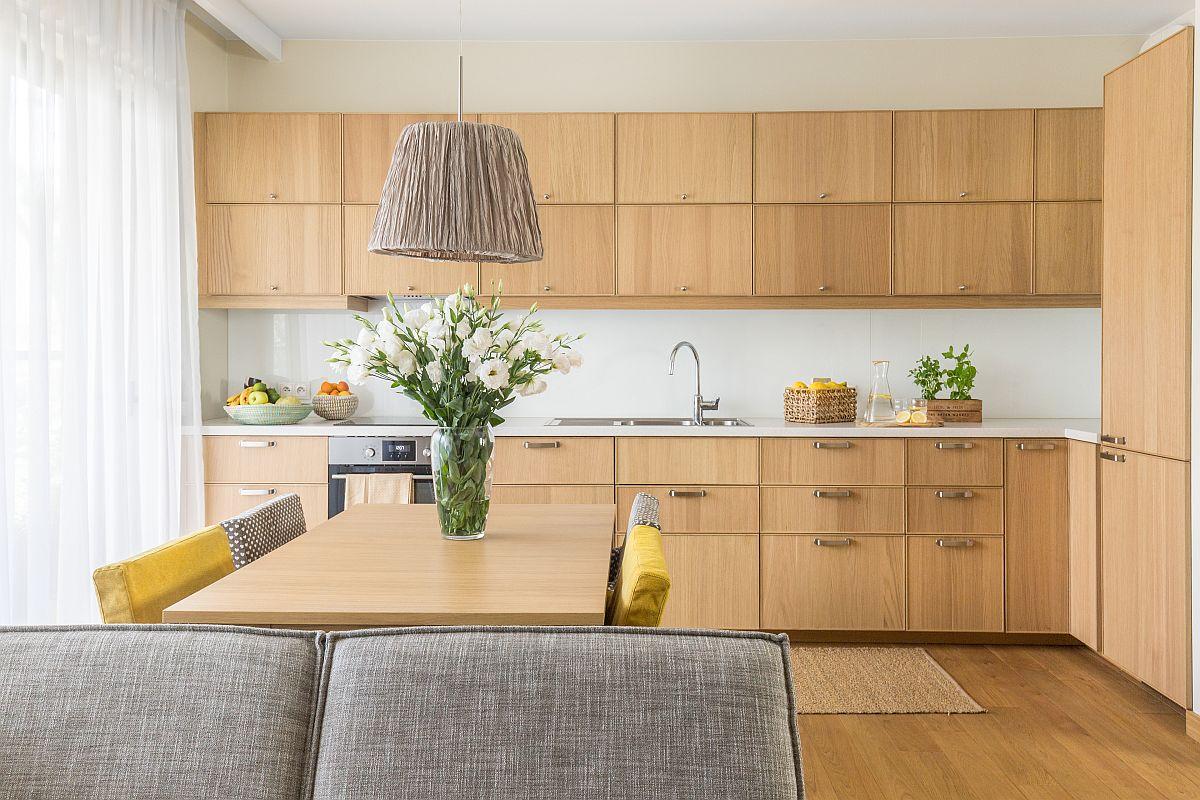 Bucătăria este furniruită cu un tip de stejar similar parchetului, astfel că în ansamblu suprafața pardoselii pare să se continue pe verticală și la nivelul corpurilor de mobilier. Blatul și peretele bucătăriei sunt îmbrăcate în același material compozit alb pentru ca aspectul să fie cît mai curat și ordonat și să oferă un respiro în ansamblul prea asortat al corpurilor de mobilier. De asemenea, înălțimea la care au fost poziționate corpurilor suspendate nu depășește înălțimea tâmplăriei ferestrelor, ci pare să o continue. Un detaliu important în percepția camerei.
