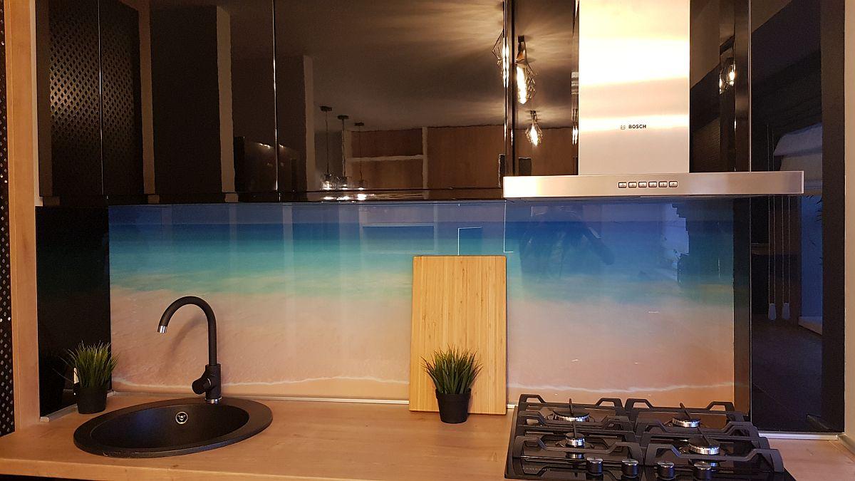 Peretele bucătăriei, în zona de lucru, este placat cu sticlă printată în loc de faianță. Sticla a fost realizată pe comandă de către firma Movi Design, cea care a executat și mobilierul.