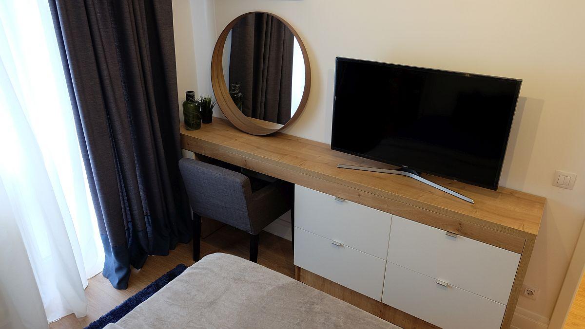 În fața patului a fost prevăzută o comodă cu triplu rol: masă de toaletă, loc de tv și depozitare cu sertare. Oglinda rotundă este de la IKEA, scaunul de la Somproduct, iar comoda realizată pe comandă la Movi Design, conform proiectului arhitectei Andreea Beșliu.