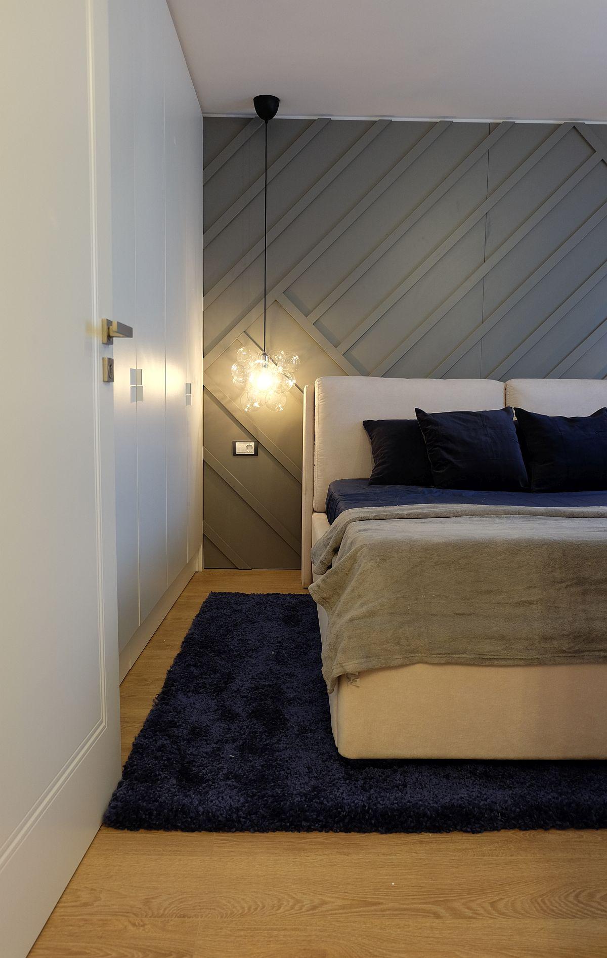 Dormitorul este amenajat de tip matrimonial cu un pat pe centrul și spații de depozitare din plin. În spatele patului, peretele a fost decorat cu baghete din polistiren și ulterior totul vopsit în aceeași nuanță de vopsea de la Dulux. Astfel, s-a creat impresia unei placări, dar evident cu costuri mai mici decât o placare efectivă din MDF. Covorul este de la Mobexpert, iar patul de la Somproduct.