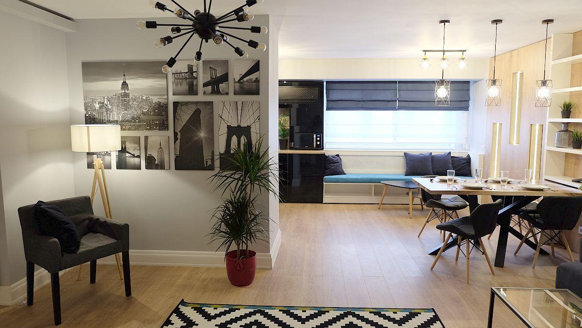 Intrarea în locuință coincide cu cea în spațiul zonei de zi, iar ceea ce se vede prima dată este sufrageria, bancheta de la fereastră și zona de canapea din living.