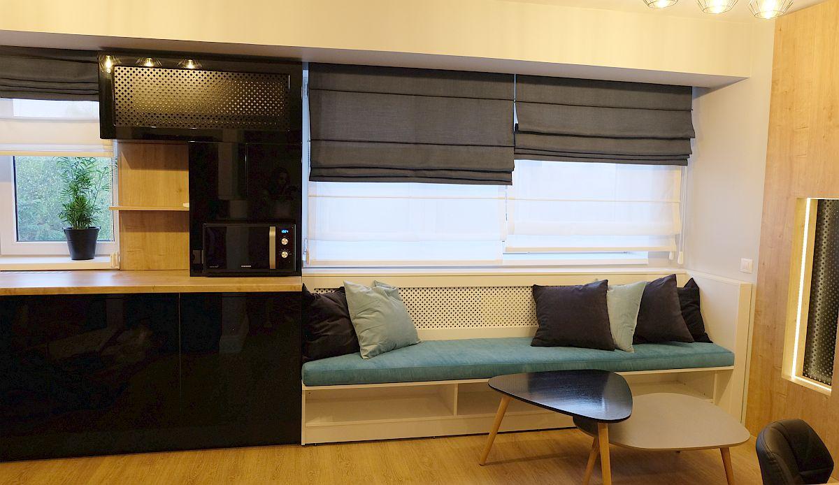 În dreptul ferestrei și în continuarea mobilierului de bucătărie a fost gândit un loc de banchetă, numai bun pentru lectură, pentru savurat cafeaua de dimineață sau pur și simplu pentru a privi pe fereastră. Bancheta a fost realizată pe comandă, la fel ca și mobilierul bucătăriei la firma Movi Design. Pnetru ferestre au fost prevăzute storuri romane realizate pe comandă de către designerul Alina Țâru.