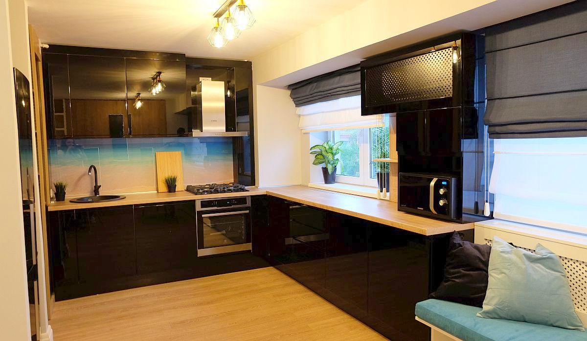Bucătăria este organizată cu un blat în formă de L, cu instalațiile dispuse pe un singur perete. Frigiderul, de sine stătător, este mascat într-o nișă configurată în peretele parțial din gips-carton care separă bucătăria de living. Mobila de bucătărie este din PAL negru lucios realizată pe comandă de firma Movi Design, conform proiectului arhitectei Andreea Beșliu.
