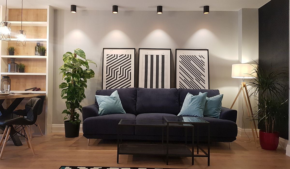 Locul canapelei este pus în evidență și prin iluminatul artificial. În lateralul ei, pe peretele comun cu cel al ușii de la intrare, peretele este placat cu un panou traforat vopsit în negru, care dă senzația de adâncime. Canapeaua este de la Euromobila, măsuța de la IKEA, plantele și măștile de ghiveci de la Florăria Trias, lampadarul de la Eglo, iar tablourile sunt realizate pe comandă.
