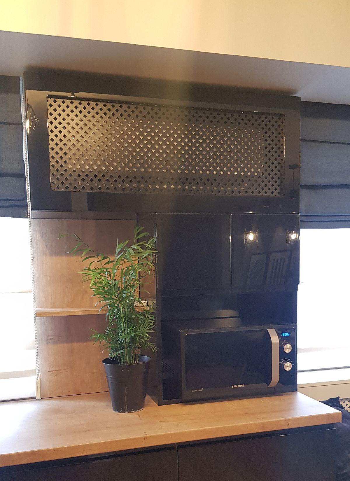 Aparatul de aer condiționat situat între ferestre este mascat cu un panou traforat vopsit negru lucios la fel ca și mobila din bucătărie.