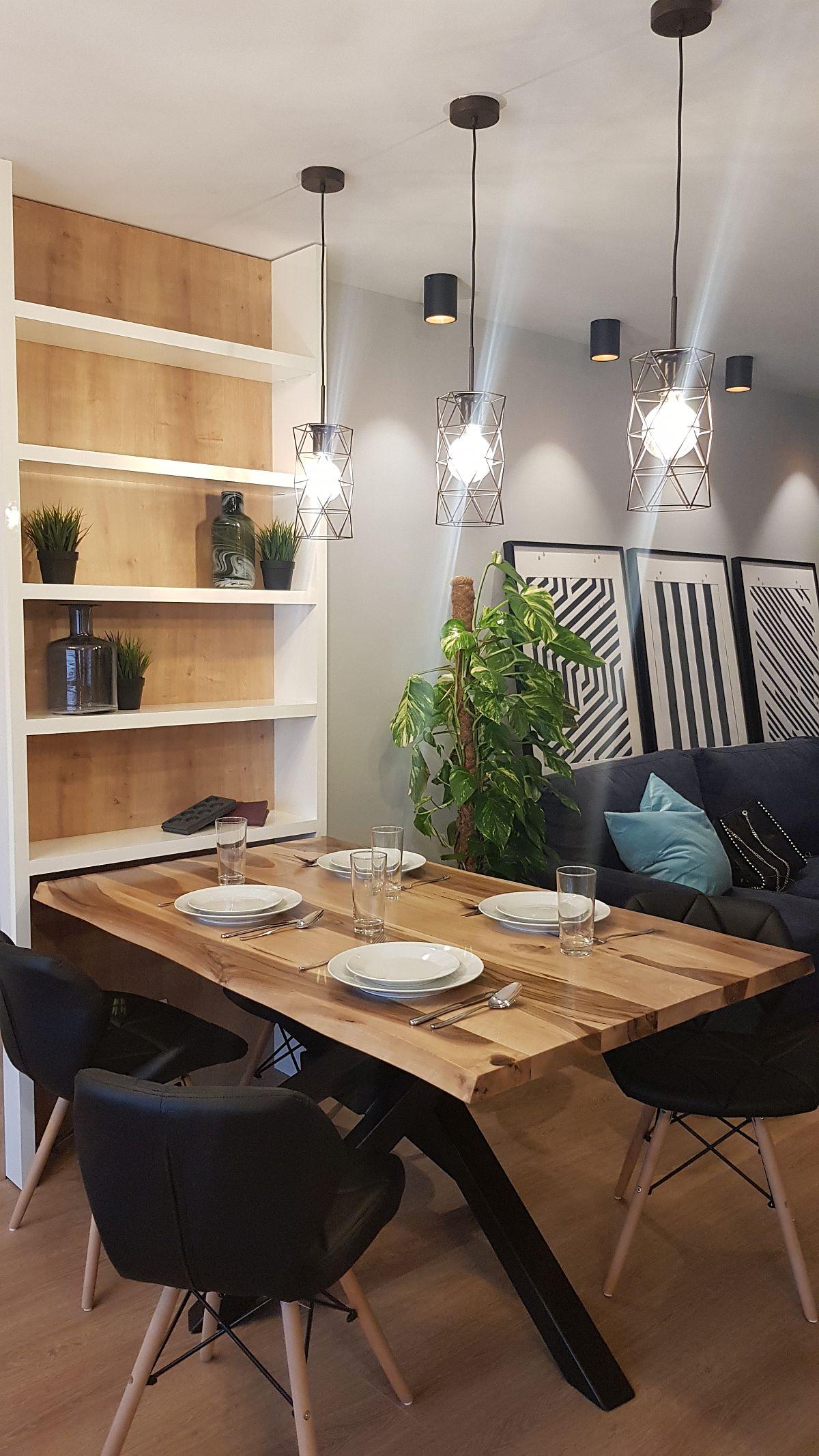 Locul de luat masa este situat la granița dintre living și bucătărie, marcat atât prin mobilier specific, cât și prin corpurile de iluminat suspendate deasupra mesei. Pe verticală a fost prevăzută o etajeră cu rafturi care pot avea dublu rol: pentru cărți sau pentru veselă. Masa a fost achiziționată de la Wood, scaunele de la Somproduct, iar corpurile de iluminat de la Eglo.