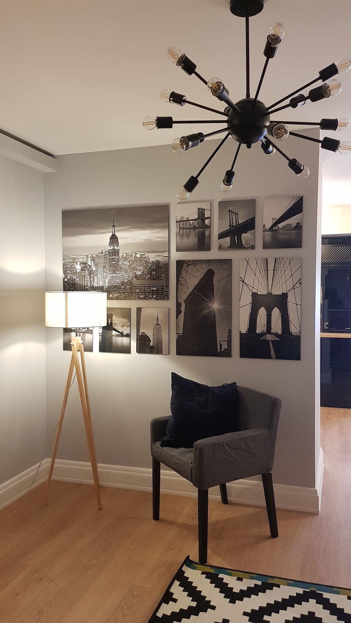 Peretele parțial dintre living și bucătărie este decorat cu imagini alb negru. Dacă se dorește, se poate instala în zonă un lampadar și un scaun confortabil pentru extra loc de ședere la tv. Fotografiile sunt de la IKEA, lampadarul de la Eglo, iar scaunul de la Somproduct. Corpul de iluminat din living este de la NeonLighting.