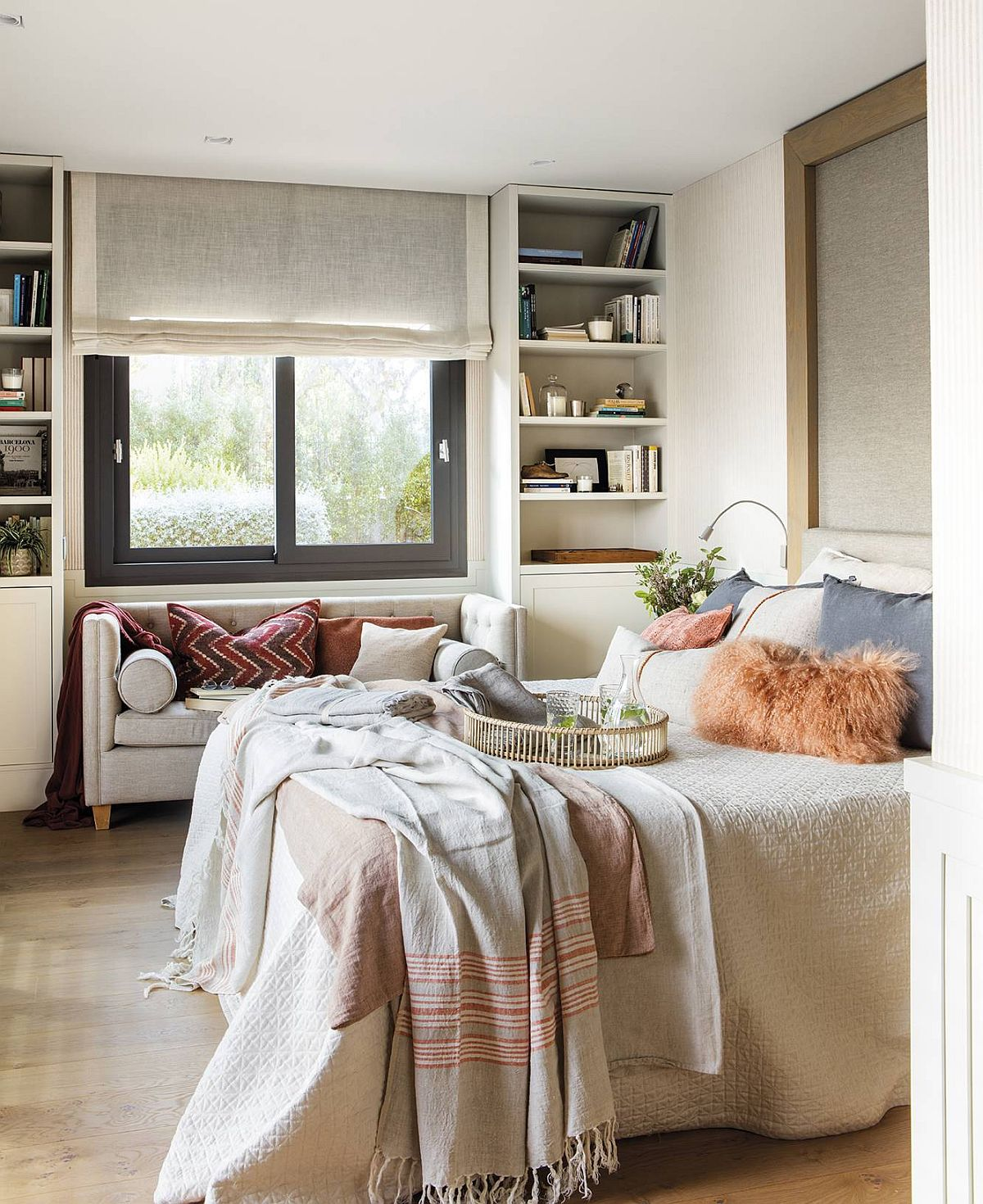 Aceeași linie a finisajelor și culorilor este continuată și ăn dormitor, unde spațiile de depozitare încadrează fereastra, deasupra având rafturi. Separat există un dressing, dar cert este că atmosfera finală este una de calm obținută prin simplitatea liniilor și prin alegerea unor decorațiuni textile plăcute, confortabile, prin care s-au adus și pete de culoare în ambient.