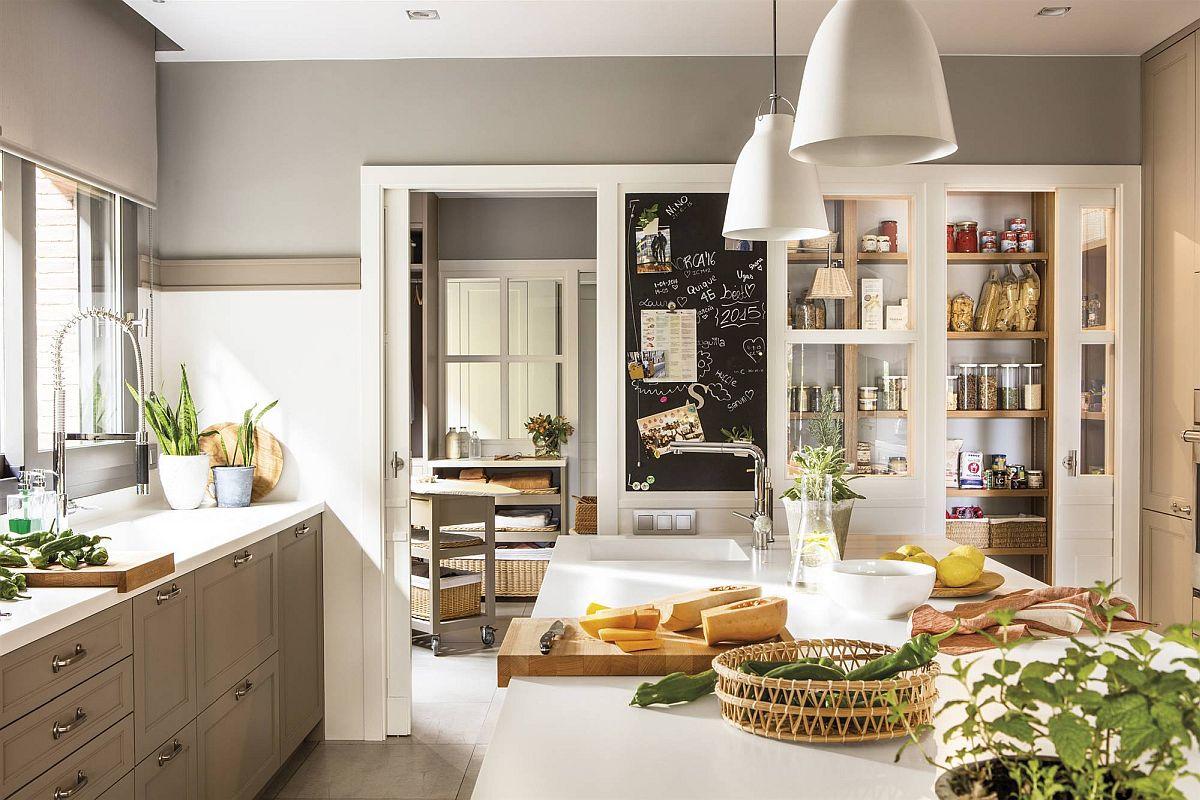 Legătura dintre bucătărie și spațiile anexe, spălătorie și cămară este evidentă din acest unghi. Spațiile sunt separate față de bucătărie prin uși culisante, gândite încă din faza de proiect a casei. Partea de sus a ușilor are geam pentru o vizualizare mai bună, dar și pentru ca lumina naturală să fie prezentă din plin.