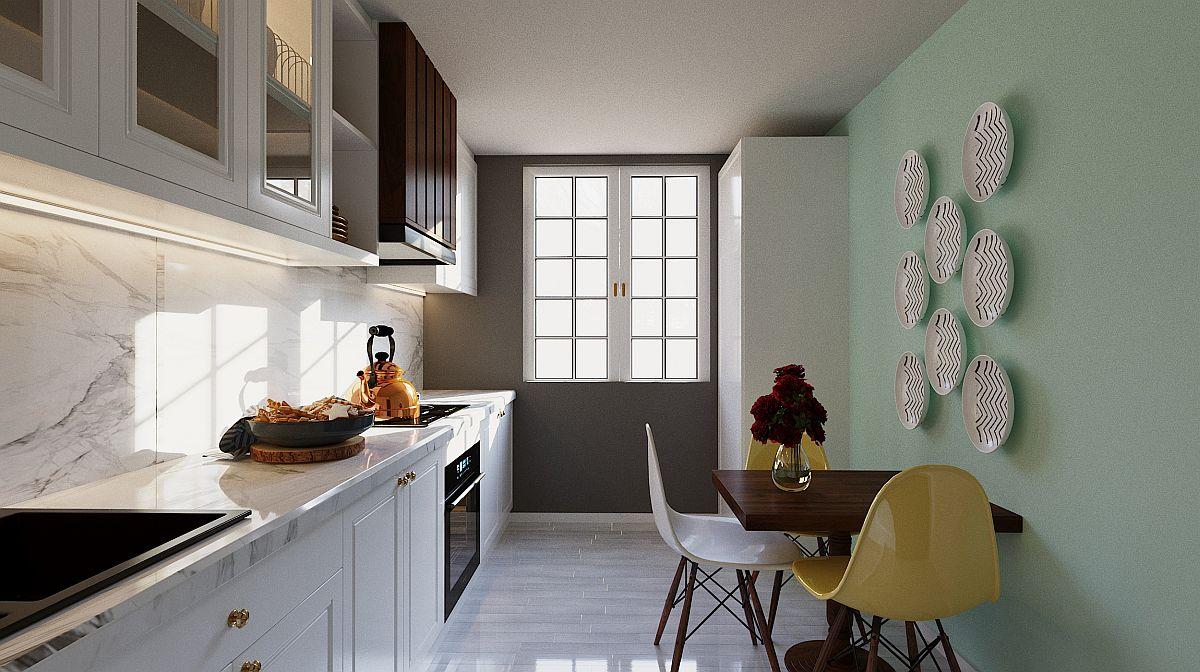 Bucătăria gândită de către Andreea Beșliu include și un loc de luat masa, peretele din zonă fiind decorat cu o nuanță relaxantă de verde mentă.