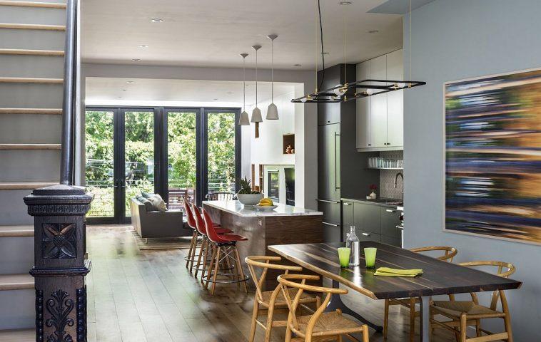 Parterul lung și ăngust este de fapt un spațiu unde funcțiunile comunică între ele. Între livingul formal și bucătărie există zona de sufragerie, prima vizibilă de fapt la intrarea în casă, ceea ce face ca interiorul să devină mai ospitalier, primitor. Pentru a sublinia zona, dar și pentru a o lega de partea din față și cea din spate, au ales o zugrăveală într-o nuanță de albastru. Practic, prin finisaje simple de tipul zugrăvelilor cu vopseluri lavabile s-au mai redus din costuri, comparativ cu a alege tapete sau placări ori ornamente pe perete.