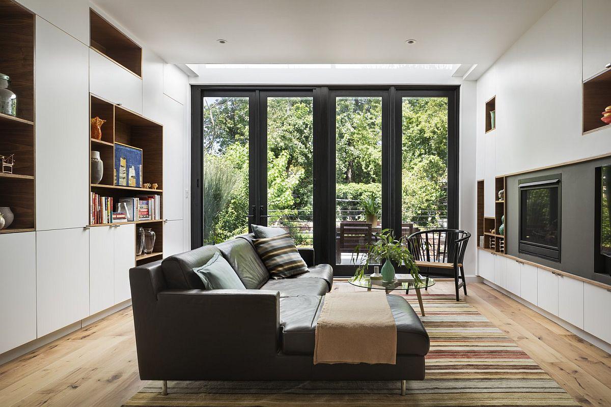 Livingul folosit în mod curect de familie, unde este integrat și televizorul are un mobilier realizat cu carcase de la IKEA, și cu ușile și nișele făcute pe comandă. Pereții au fost tratați similar unor ansambluri de depozitare neutre pentru a direcționa atenția asupra vegetației care se vede prin ferestrele ample.