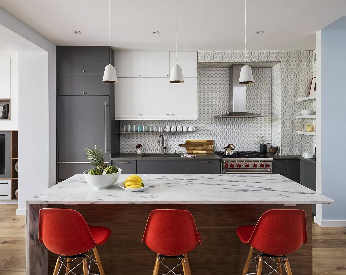 Schema cromatică de bază în întreaga locuință este de alb, gri și nuanțe d elemn. Aceste texturi și nuanțe a permis inserarea cu ușurință a accentelor de culoare. Spre exemplu, la bucătărie scaunele roșii de la masa tip insulă adaugă fix pata de culoare necesară.