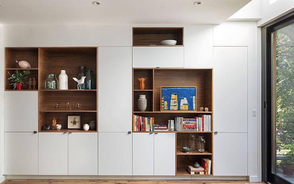 În living ambii pereții sunt folosiți pentru mobilier, iar spațiul de depozitare este foarte generos. Jocul de gol și plin asigură însă o imagine ordonată și totodată inedită. Când banii sunt numărați simplitatea este cea mai bună metodă în privința liniei mobilierului.