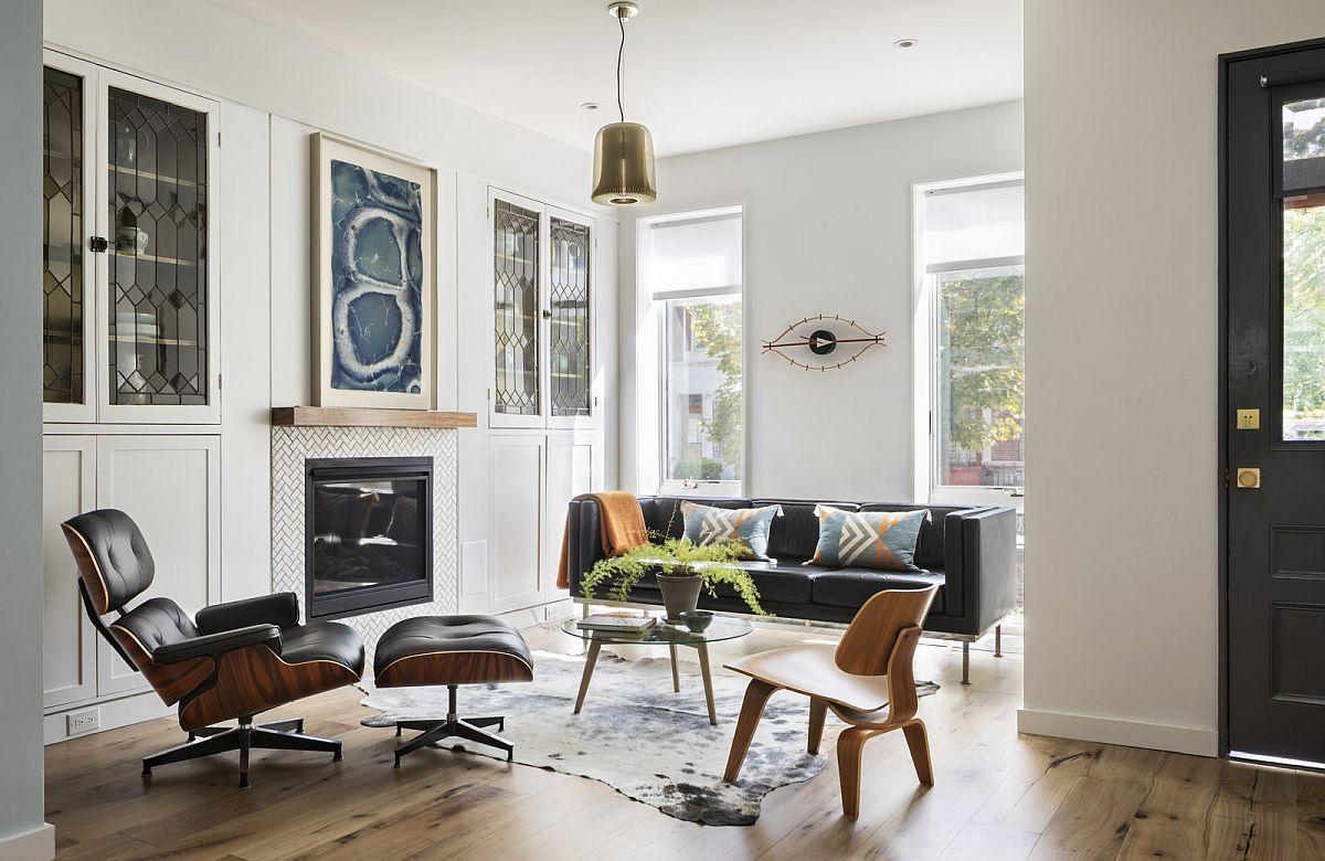 Imediat după holul de la intrare există un living formal ambient în stil eclectic. Vechile geamuri cu plumb ale ferestrelor eua devenit acum parte integrantă din mobilă realizată pe comandă care încadrează șemineul. Piesele semnate de designerii Eames completează frumos livingul de primire.