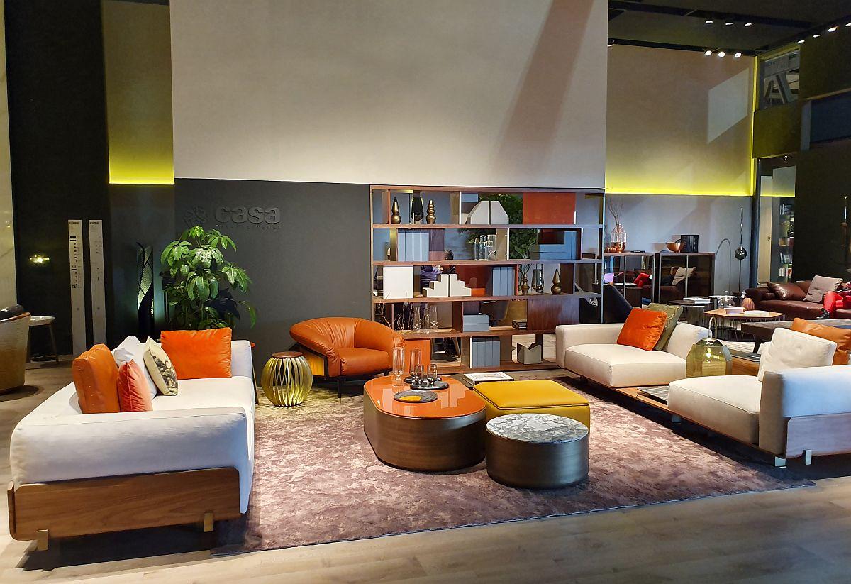 Câteva piese mici de mobilier în portocaliu asortate cu perne decorative în nuanțe similare schimbă percepția asupra unui spațiu mobilat și tratat neutru.