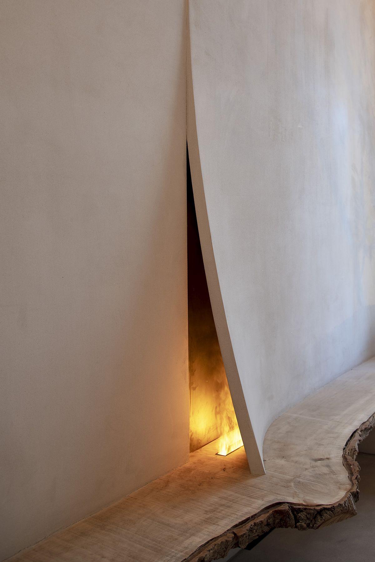 O piesă spectaculoasă este șemineul, dar care este realizat integral manual, după conceptul arhitectei. În blatul din lemn masiv de la Detarima, este inserat un recipient pentru bioetanol, flacăra acestuia fiind parcă protejată de un pliu al peretelui finisat cu tencuieli speciale de la Cine Valentine Pinturas.