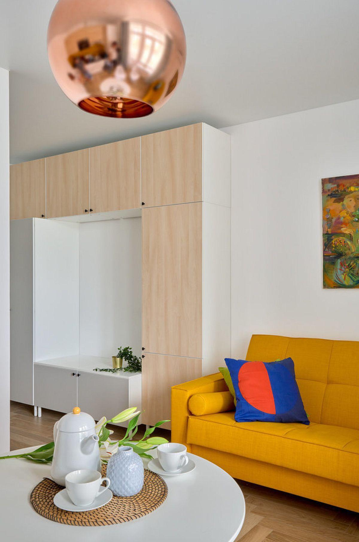 Practic, cea mai lungă latură a garsonierei a fost gândită pentru piesele de mobilier care au la rândul lor o lungime mare: ansamblul de dulapuri și canapeaua.