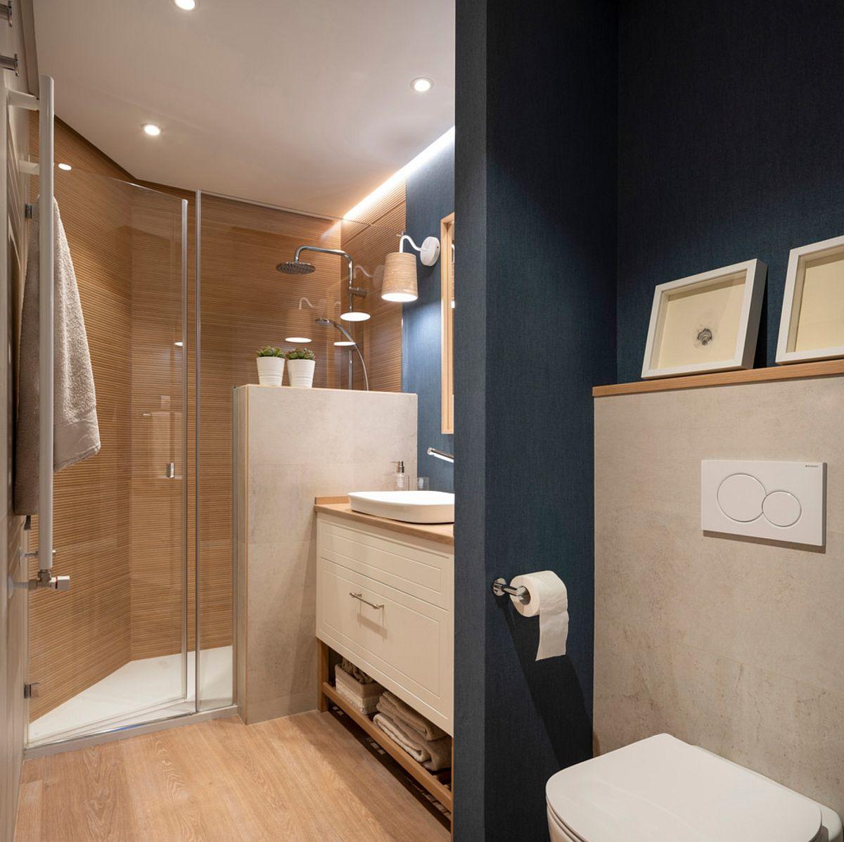 Spațiul lung și îngust a fost exploatat pentru înșiruirea funcțiunilor din baie. Între duș și vasul de toaletă un generos mobilier realizat ep comandă după proiectul designerilor asigură necesarul pentru depozitare.