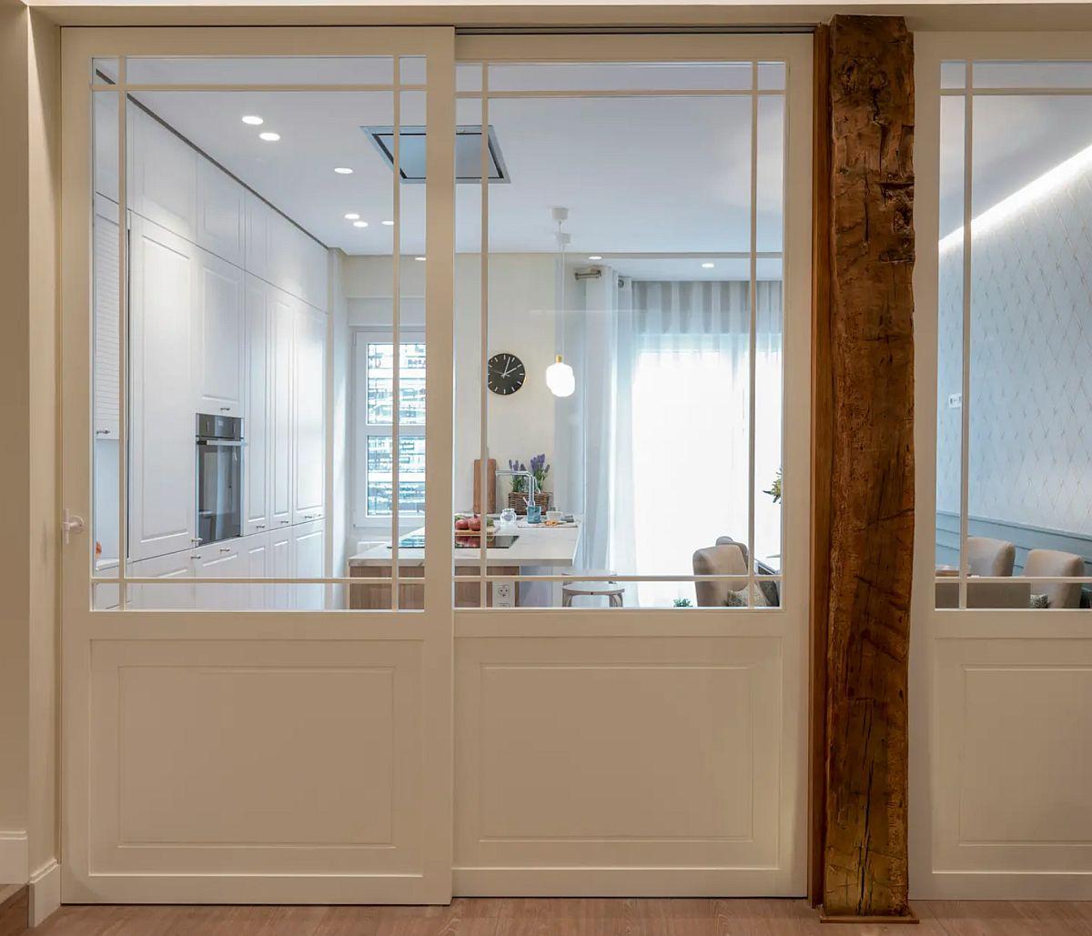 Proprietarii și-au dorit o bucătărie generoasă, dar neapărat separată. Designerii au venit cu ideea unor uși culisante în dreptul bucătăriei și a aunui panou fix în dreptul locului de luat masa (după stâlp).
