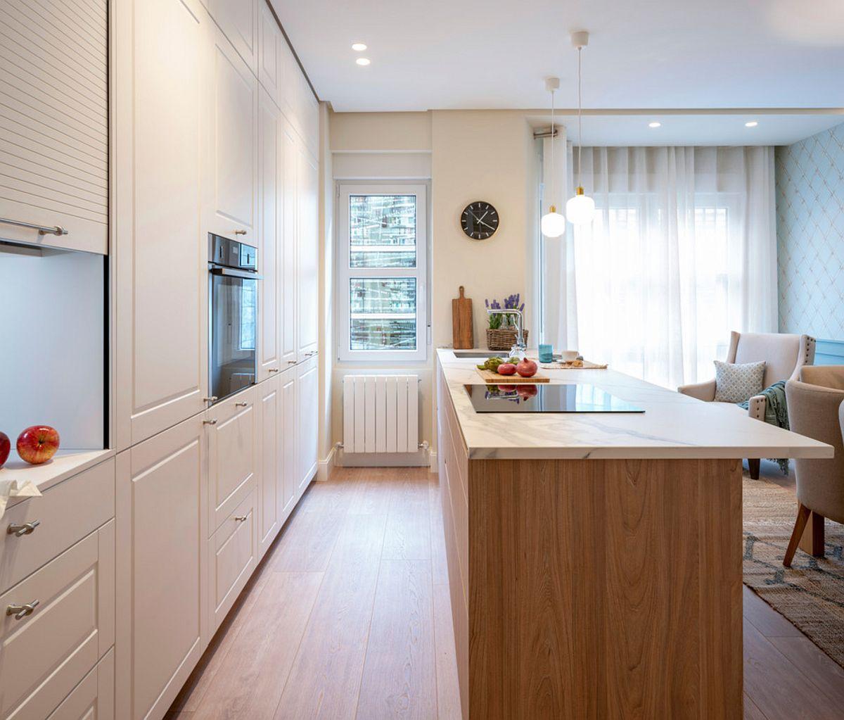 Inițial bucătăria era până la limita barului, evident îngustă. Acum, deschisă către fostul living, a devenit mult mai luminoasă. În plus designerii au putut gândi aici multe spații de depozitare. Bucătăria este realizată pe comandă la firma Santos Cucinas.