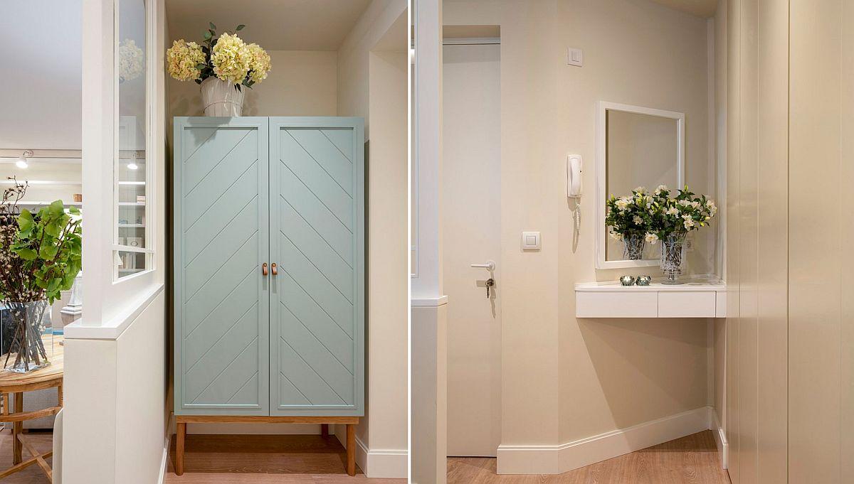 Încă de la intrarea în locuință modificările se fac simțite. În locul fostului hol lung și îngust, acum ușa de la intare este separată parțial cu ajutorul unui parapet și al unei ferestre interioare, practic un paravan constructiv. Un dulap servește pe post de cuier, iar în lateralul ușii, la îndemână, este configurată o poliță în dreptul unui generos ansamblu de depozitare.