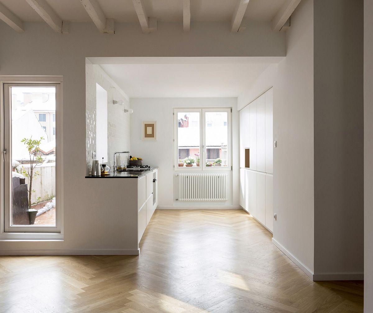 Prezența mai multor ferestre, dintre care una chiar în zona de lucru, poate împiedica adoptarea soluției corpurilor suspendate. Varianta cu blat și corpuri inferioare sub fereastră, iar paralel un ansamblu ce încorporează și electrocasnicele mari este una ce poate funcționa foarte bine.