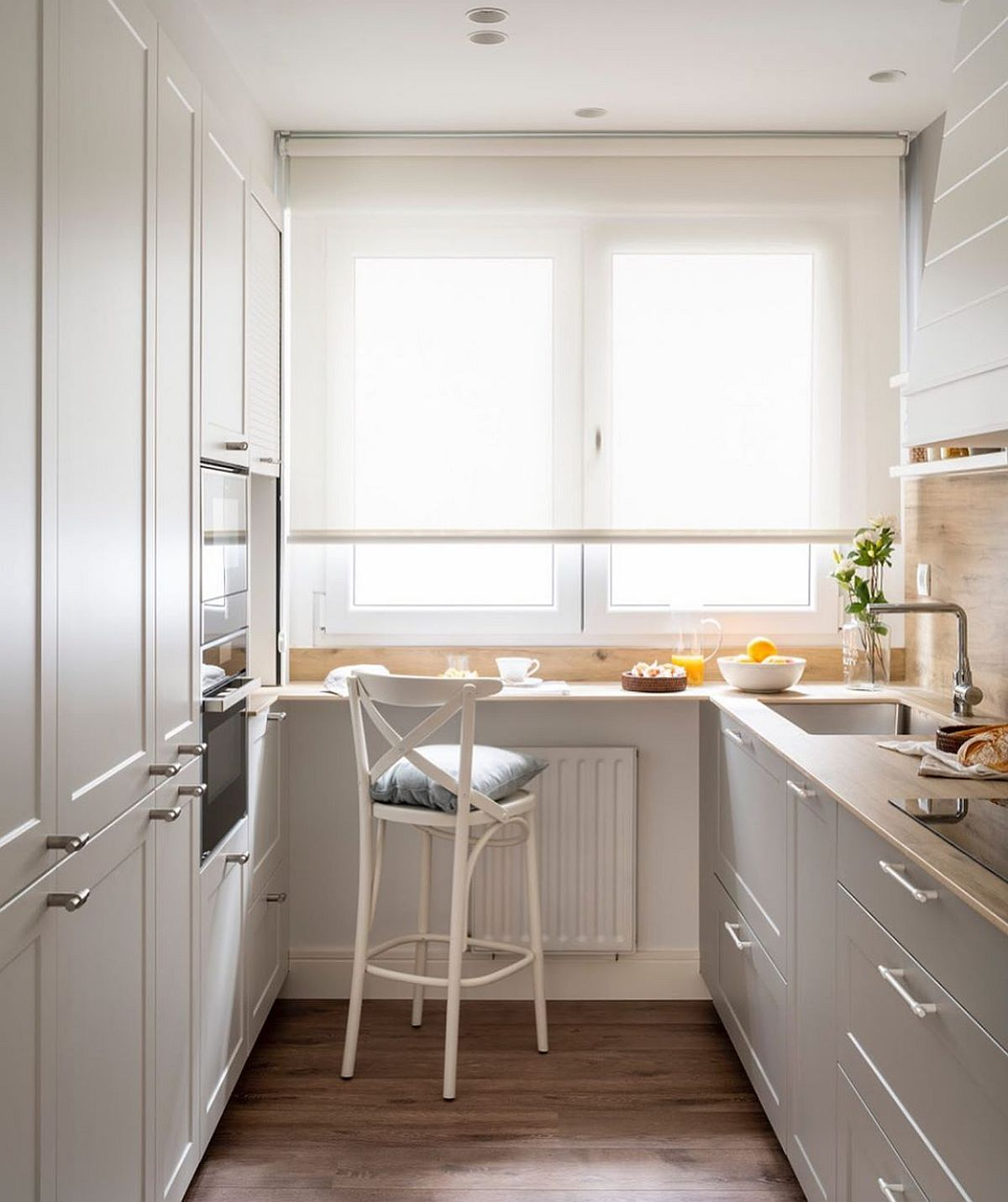 Când există o lățime suficientă pe partea opusă peretelui cu instalații, aici se poate gândi un ansamblu de mobilier până în plafon, unde să fie incluse atât electrocasnicele mari (combină frigorifică, cuptoare), cât și spațiile de depozitare a veselei și a alimentelor.
