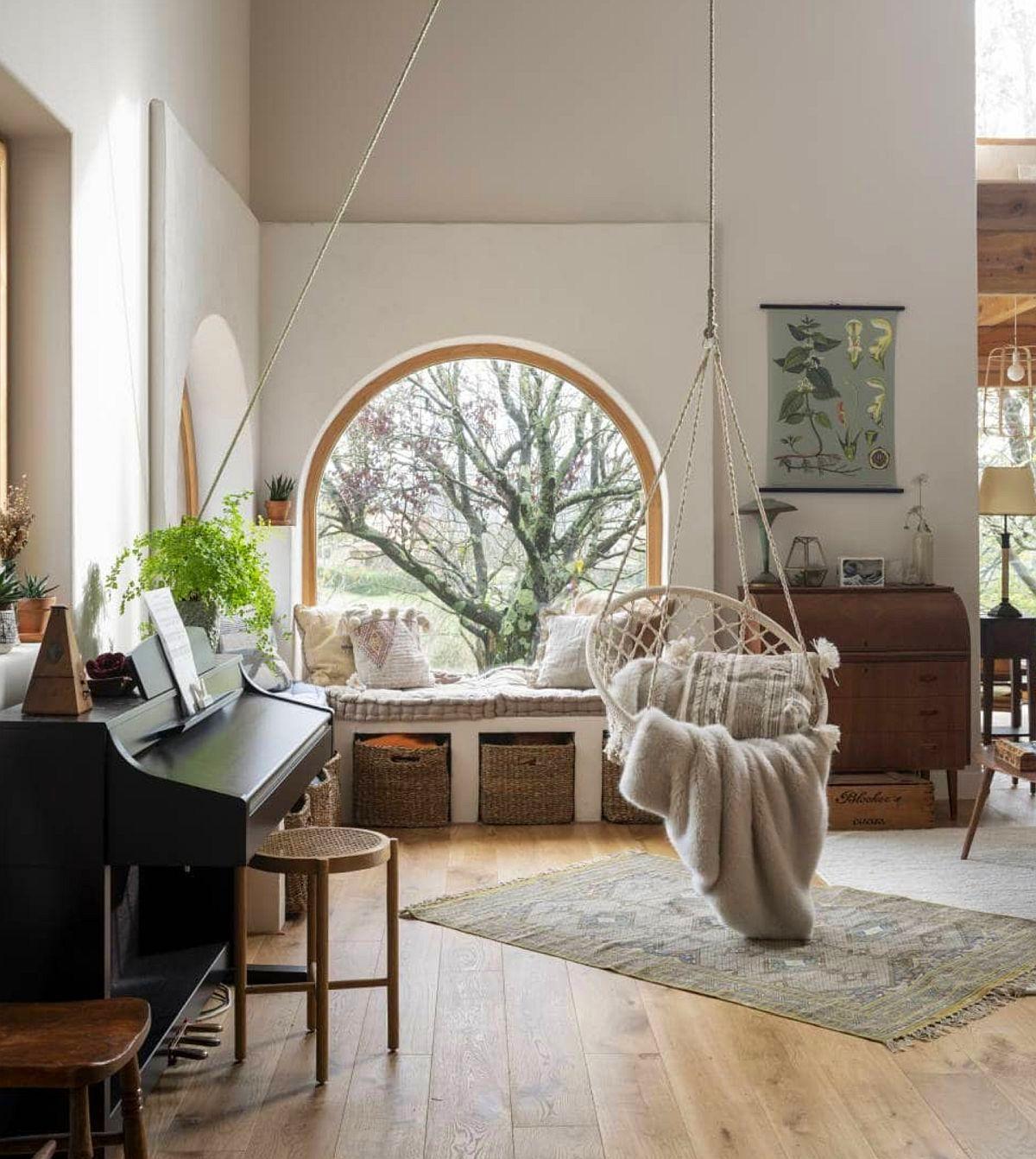 Una dintre ferestrele în arcadă se citește imediat de la intrarea în casă, ca atare, designerul a prevăzut ca locul să fie marcat fruos și printr-un artificiu arhitectural, respectiv ferestrele pe colț să fie încadrate de o structură care să le pună în evidență, dar să le și raporteze la înălțimea umană în relație cu tavanul înalt din zonă. Prezența pianinei vorbește despre preocupările proprietarilor, un instrument care înlocuiește practic locul de tv.
