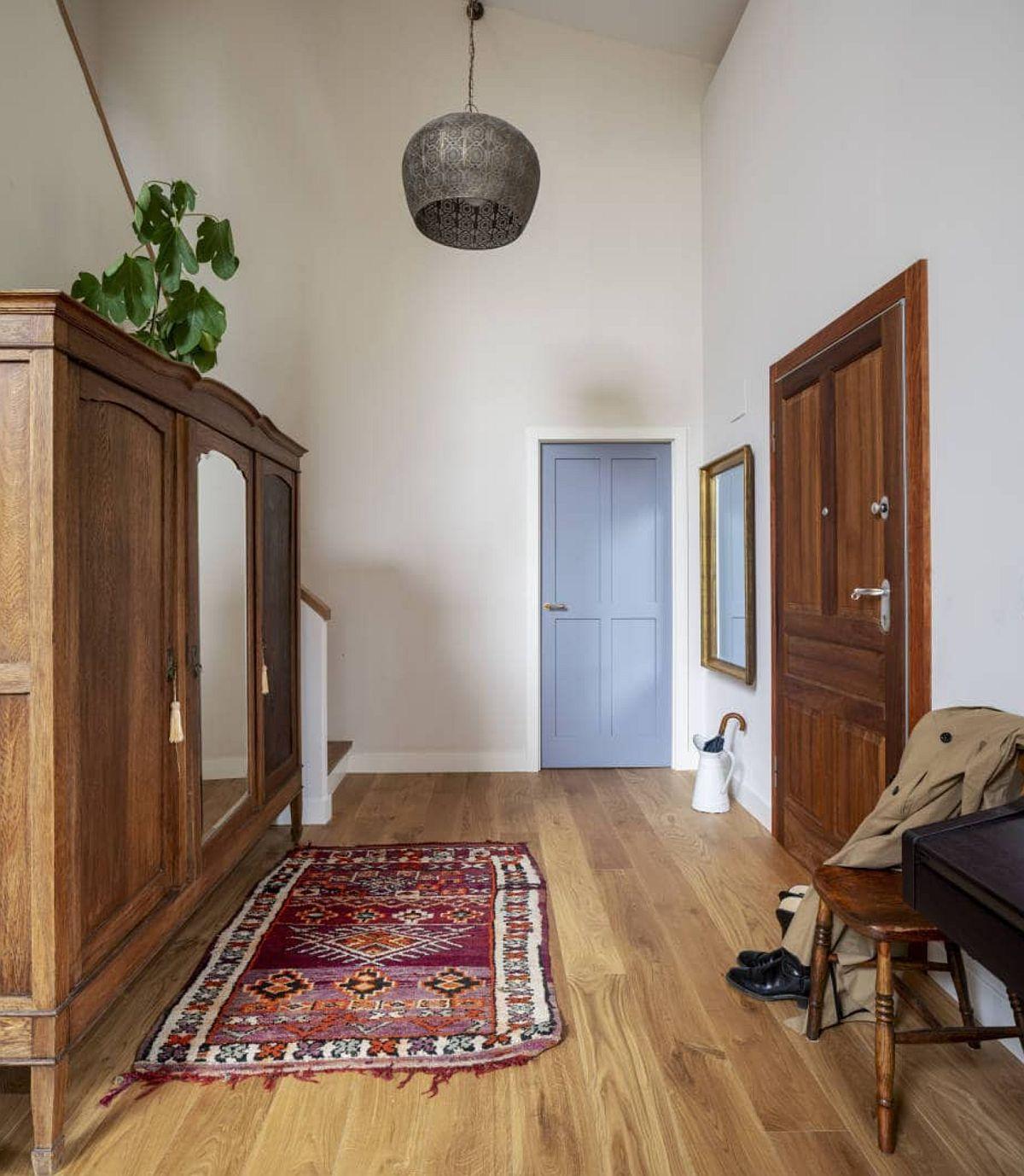 Holul de acces în casă face legătura între parterul gândit ca un spațiu deschis, între etaj la care se accede pe scara interioară și una dintre băi. Designerul a prevăzut ca pe fundalul alb al zugrăvelii, ușile interioare să se profileze frumos atât prindesenul lor, cât și prin culoarea aleasă în contrast armonios cu pardoseala din lemn.