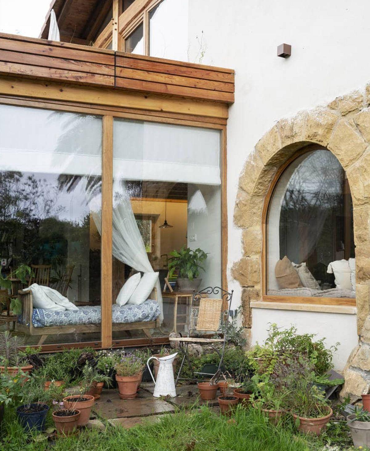 Totul pornește încă de la exteriorul casei, unde pe fundalul alb se profilează frumos arcadele îmbrăcate în piatră ale ferestrelor, dar și elementele de tâmplărie din lemn.