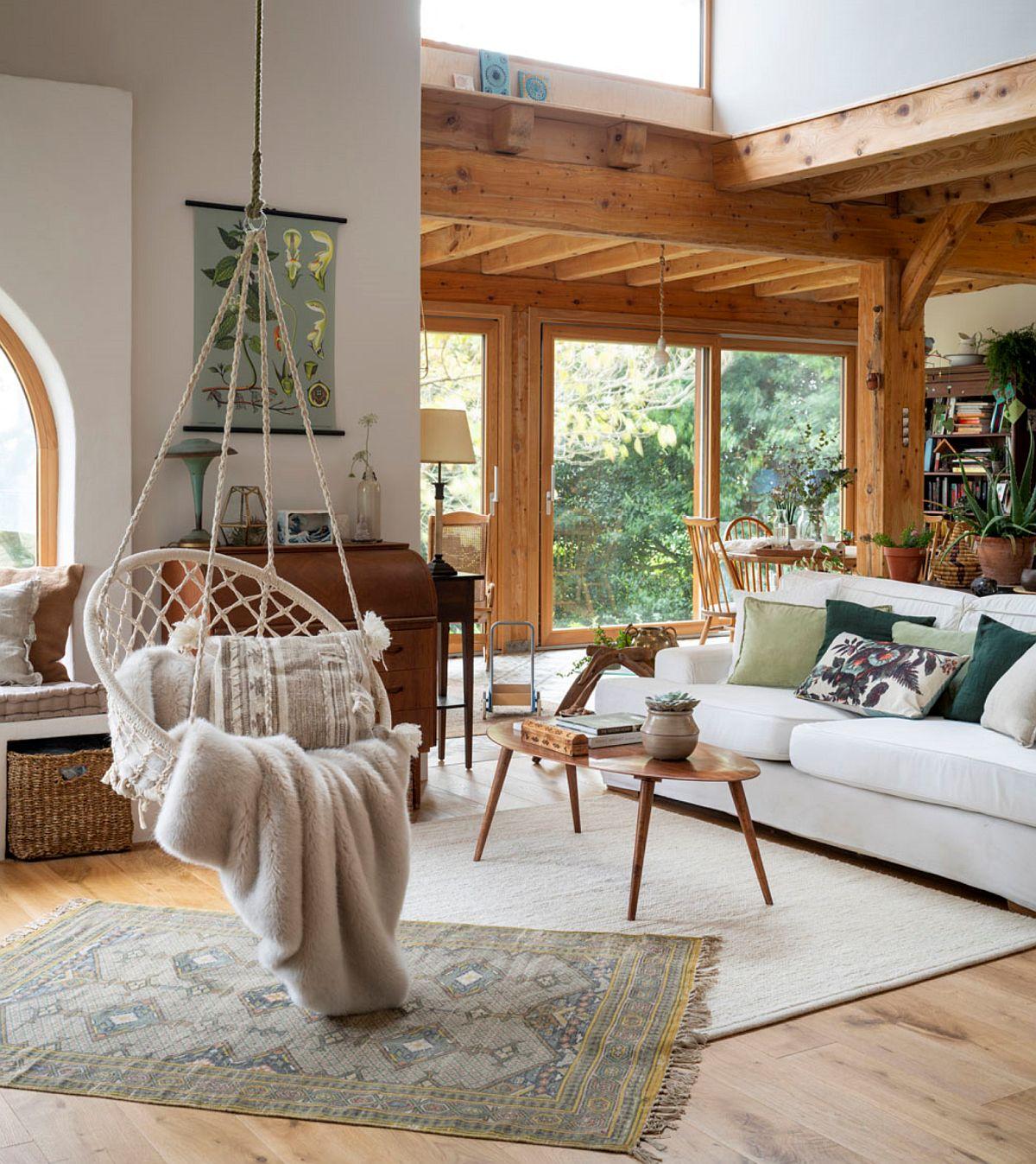 Un leagân suspendat în spațiul livingului devine punct de atracție, dar și un obiect care te face să explorezi înălțimea de aici. Practic, un loc de fotoliu reinterpretat. Un alt truc în decor, prevăzut de către stilistă este prezența covoarelor suprapuse. Unghiul și contrastul dintre ele te fac să percepți spațiul ca fiind mai mare, mai confortabil și mai ornamentat, dar totul în relație cu ferestrele mari și multe suprafețe deschise în tonuri de alburi.